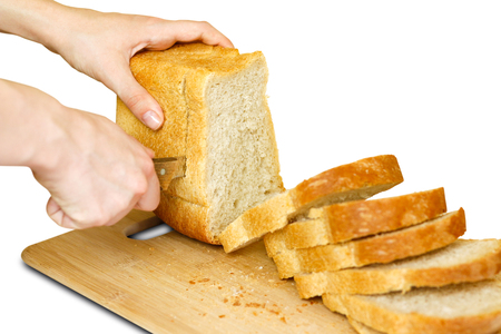 The girls hands with a knife sliced Golden bread. Isolated on white background. Stock Photo