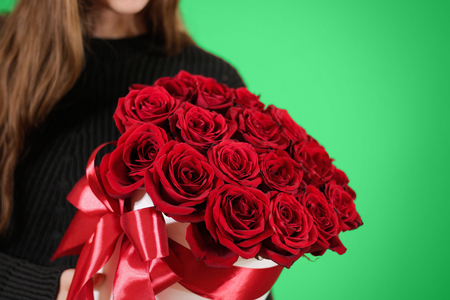 Girl in black jacket holding in hand rich gift bouquet of 21 red roses. Composition of flowers in a white hatbox. Tied with wide red ribbon and bow