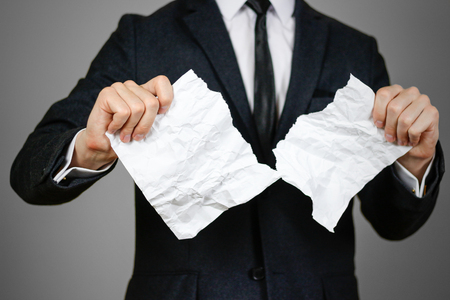 Businessman tearing hands crumpled sheet of A4 paper. Isolated on grey background.