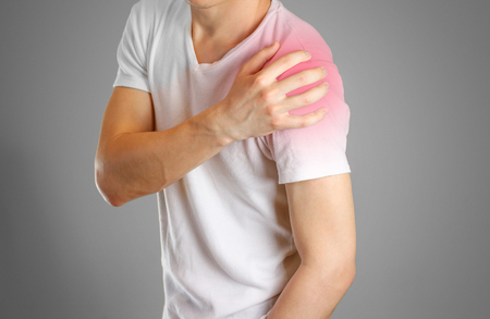 A man holds the shoulder. The pain in my arm. Sore point highlighted in red. Closeup. Isolated. Stock Photo