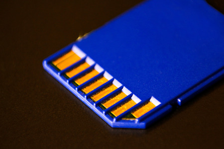 SD memory card. Blue is on the laptop Stock Photo