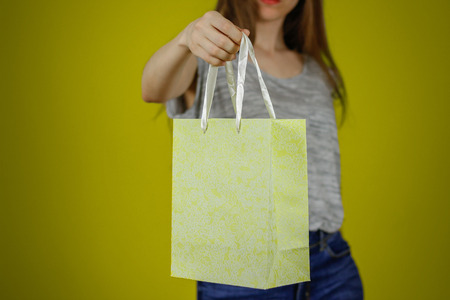 Girl holding a gift bag. Holds out a box to you. Closeup. Isolated.