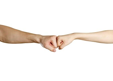 Fist to fist. Male vs female hand. Isolated on a white background. Stock Photo