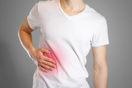Een man houdt de lever vast. Pijn in de buik. Levercirrose. Pijnpunt gemarkeerd in rood. Detailopname. Geïsoleerd.
