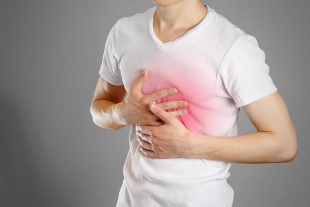Een man houdt de borsten vast. De pijn in zijn borst. Maagzuur. Buikpijn. Pijnpunt gemarkeerd in rood. Detailopname. Geïsoleerd.