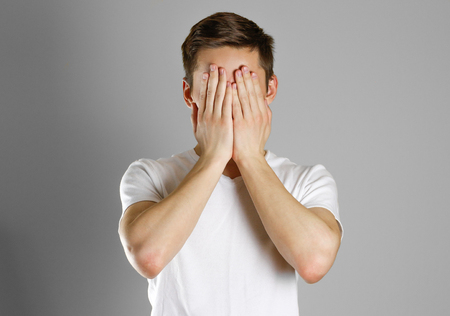 Man in white t-shirt covering his face with hands over gray background.