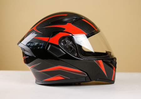 Beautiful black with red motorcycle helmet. With a transparent visor. Closeup. Isolated.