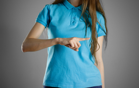 specifies: The girl in blue t-shirt pointing finger on the right. Specifies the direction. Isolated. Stock Photo