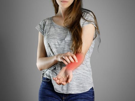 Girl in grey shirt scratching his arm. Scabies. Scratch the hand. Isolated.
