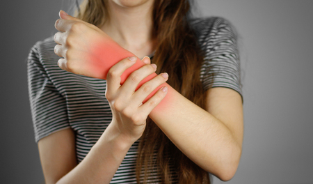 The girl has a sore elbow. The pain in my arm. Closeup. The lesion is highlighted in red. Stock Photo