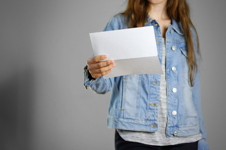 one sheet: The girl in the blue denim shirt holds the white empty piece of paper. Ready for your design. Closeup. Isolated.