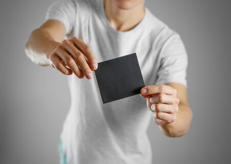 offset up: A man in a gray t-shirt holding blank clear black of the sheet. Closeup. Isolated. Stock Photo