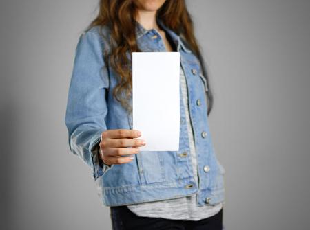 Het meisje in het blauwe denimoverhemd houdt het witte lege stuk van document. Klaar voor uw ontwerp. Detailopname. Geïsoleerd.