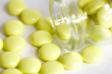 gel capsule: Yellow pills scattered around the bottle. Macro. Closeup. Isolated on a white background.