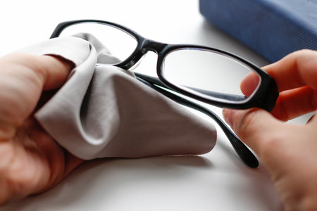 Glasses with black frame and grey wipe cloth. Closeup.