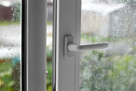 Abra la ventana de plástico blanca. En el clima lluvioso. De cerca. Foto de archivo - 85046613