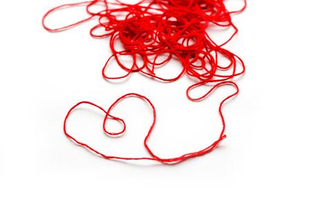 A ball of red wool yarn. Thread laid out the shape of a heart. Closeup. Isolated on white background. Banque d'images