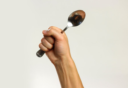 Male hands holding a metal tablespoon. Isolated on gray background. Closeup.