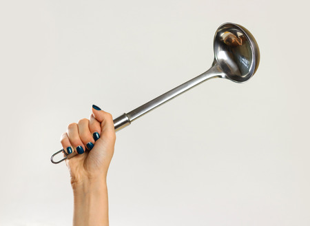 Female hands holding a metal ladle. Isolated on gray background. Closeup. Reklamní fotografie
