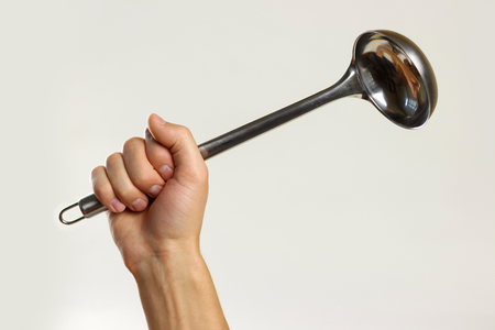 Male hands holding a metal ladle. Isolated on gray background. Closeup. Banque d'images