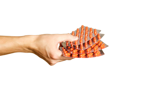Hand holding a few packets of capsules orange Stock Photo