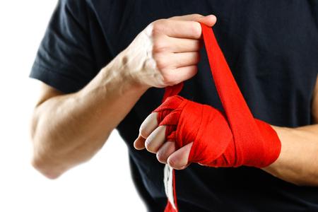 Trekt aan de rode Boxing op handverbanden. Knopen op handen sportverband. Geïsoleerd op een witte achtergrond.
