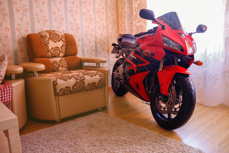 KRASNOYARSK, RUSSIA - SEPTEMBER 9, 2017: Red and black sportbike Honda CBR 600 RR 2005 PC37 in house. The motorcycle in the apartment. Winter storage.