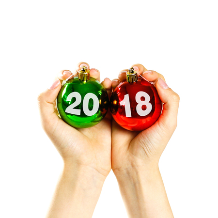 At a Christmas ball written by 2018. Hands holding Christmas ball.