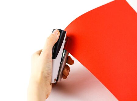 Fasten the red paper with staples on a white background. Closeup. Stock Photo