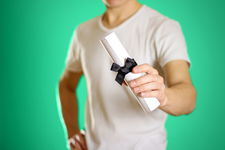 Man in hand holding scroll of white paper with a black bow on a white background. Closeup. Stock Photo