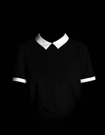 Women's simple black dress. Black dress with white collar and white sleeves. In the dark. Isolated on a black background.