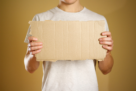 A young guy in a white t-shirt holding a piece of cardboard. Prepared for your text. Stock Photo