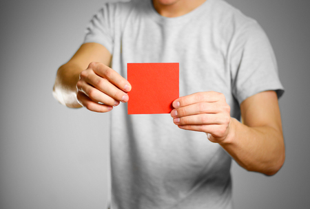 A man in a gray t-shirt holds a red clean empty square sticker. Isolated on grey background.