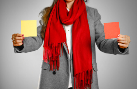 A girl in grey coat and red scarf holds a yellow and red clean empty square sticker. Isolated on grey background.
