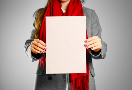 A girl in grey coat and red scarf keeps a beige clean blank sheet of A4. Isolated on grey background. Foto de archivo