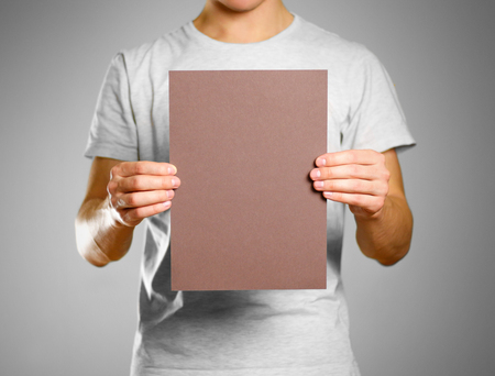 A man in a gray t-shirt keeps a brown clean blank sheet of A4. Isolated on grey background.
