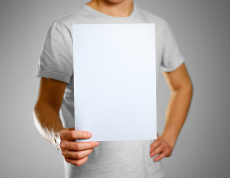 A man in a gray t-shirt keeps a light blue clean blank sheet of A4. Isolated on grey background.