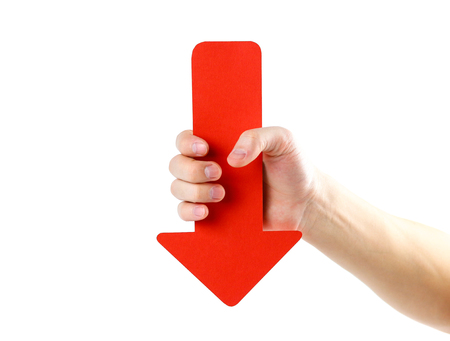A man's hand holds a large red arrow. Close up. Isolated on a white background.