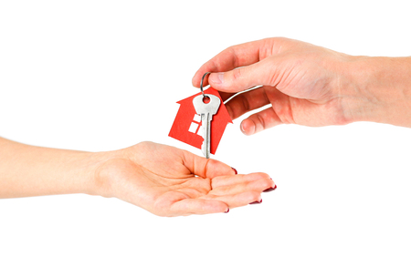 The hand holds the keys with the red house keychain. Purchase of apartments. House in hands. Close up. Isolated on a white background. Imagens