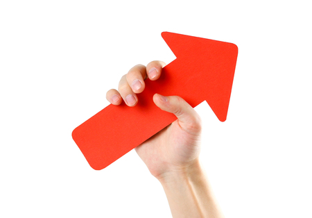 A mans hand holds a large red arrow. Close up. Isolated on a white background. Stock Photo