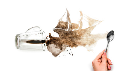 The hand draws a ship. Spilled coffee in the shape of a ship. Brown ship on white paper. Close up. Isolated background.