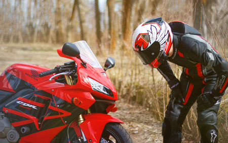 KRASNOYARSK, RUSSIA - April 21, 2018: Beautiful motorcyclist in full gear and helmet on a red and black Honda 2005 CBR 600 RR (PC37). Editorial