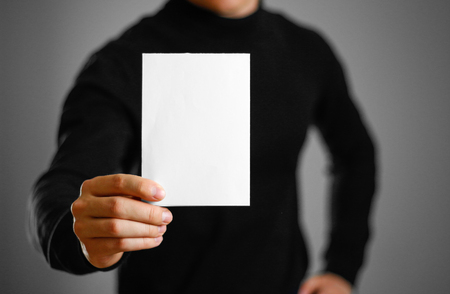 Man showing blank white flyer brochure booklet. Leaflet presentation. Pamphlet hold hands. Man show clear offset paper Reklamní fotografie