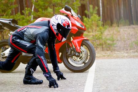 KRASNOYARSK, RUSSIA - April 27, 2018: Beautiful motorcyclist in full gear and helmet on a red and black Honda 2005 CBR 600 RR (PC37).