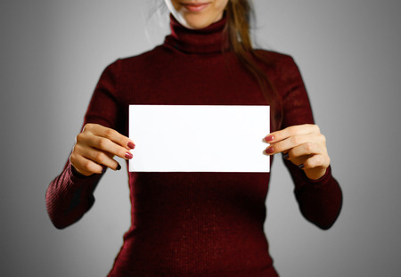 Woman showing blank white flyer paper. Leaflet presentation. Pamphlet hold hands. Girl show clear offset paper. Sheet template