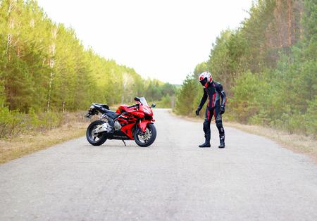 KRASNOYARSK, RUSSIA - April 27, 2018: Beautiful motorcyclist in full gear and helmet on a red and black Honda 2005 CBR 600 RR (PC37)