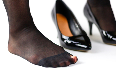 The girl in the torn shoes and black nylon pantyhose. Isolated on white background.