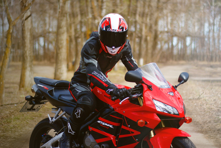 KRASNOYARSK, RUSSIA - April 21, 2018: Beautiful motorcyclist in full gear and helmet on a red and black Honda 2005 CBR 600 RR (PC37)