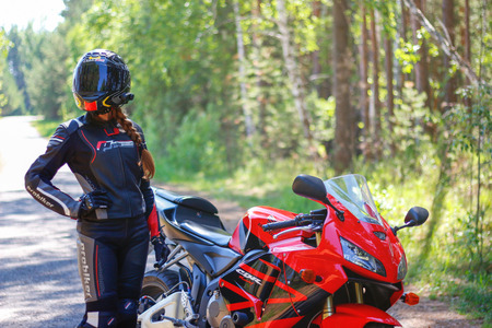 KRASNOYARSK, RUSSIA - June 23, 2018: Beautiful girl motorcyclist in full gear and helmet on a red and black Honda 2005 CBR 600 RR (PC37) Éditoriale