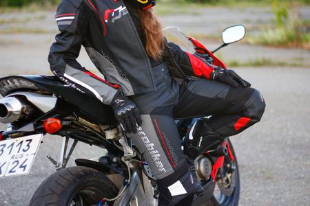 KRASNOYARSK, RUSSIA - June 23, 2018: Beautiful girl motorcyclist in full gear and helmet on a red and black Honda 2005 CBR 600 RR (PC37) Editorial